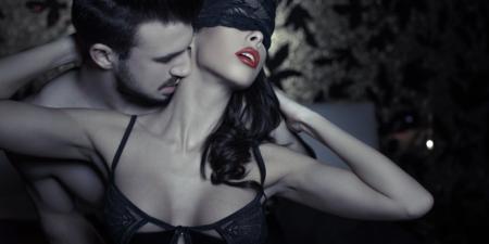 un homme embrasse le cou d'une femme qui porte un masque, avant de lui faire l'amour