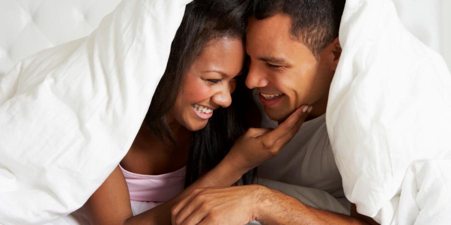 un couple hétéro souriant et à l'aise sous la couette d'un lit